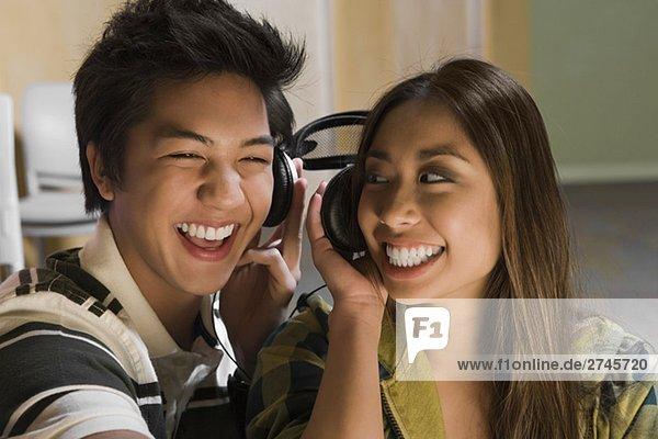 Nahaufnahme eines jungen Paares Musikhören und lächelnd