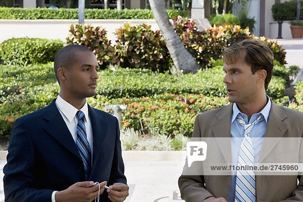 Two businessmen talking to each other