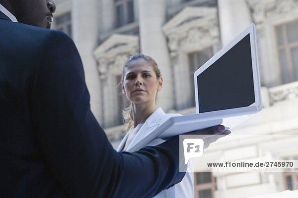 Seitenprofil des mit einem Laptop mit einer vor ihm stand geschäftsfrau kaufmann