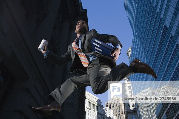 Low angle view of a businessman running in mid-air