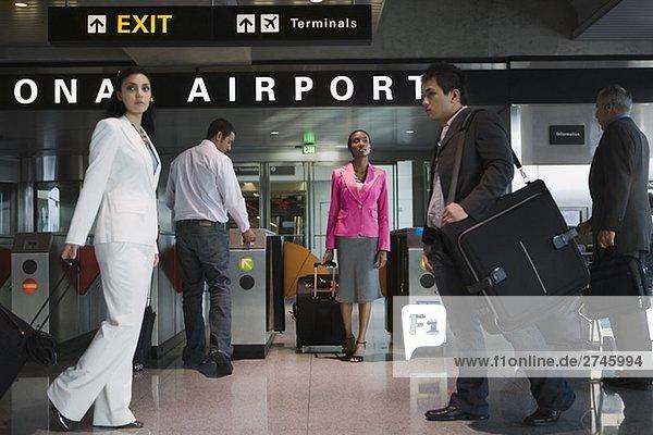 Fünf Menschen zu Fuß auf einem Flughafen