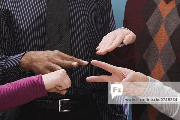 Vier Führungskräfte in Unternehmen machen Hand Zeichen
