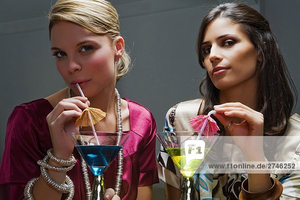 Portrait of two young women drinking cocktail