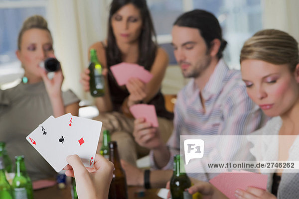 Young man with her friends playing cards