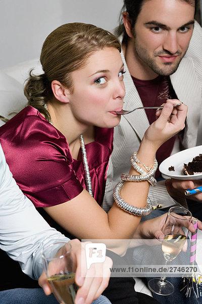 Portrait einer jungen Frau Kuchen essen und sitzen mit ihren Freunden