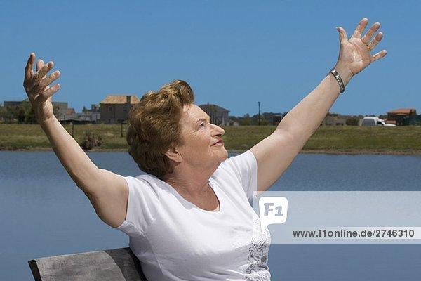ältere Frau sitting am Seeufer mit ausgestreckten Armen