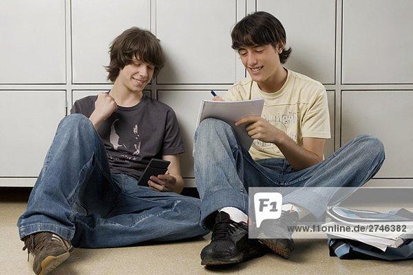 Junger Mann mit ein Teenager zu sitzen und Schreiben auf einem notebook