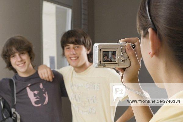 Nahaufnahme eines Teenagerin nehmen ein Foto ihrer zwei Freunde mit einer Digitalkamera