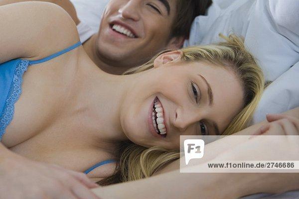 Porträt eines jungen Paares auf dem Bett liegend und lächelnd