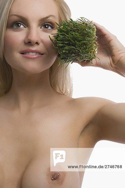 Nahaufnahme of a junge Frau hält Wheatgrass und lächelnd