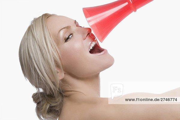 Nahaufnahme of a junge Frau hält ein Megaphon an ihr Gesicht