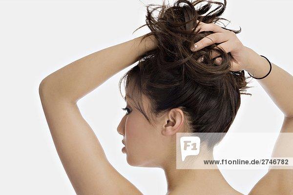 Nahaufnahme einer jungen Frau mit ihren Händen im Haar