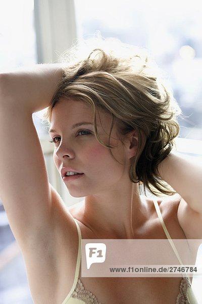 Nahaufnahme einer jungen Frau mit der Hand im Haar