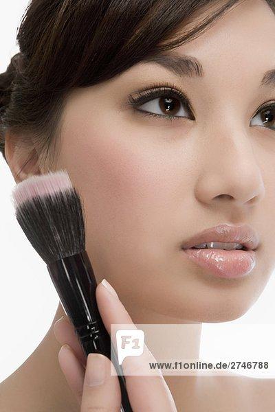 Nahaufnahme of a junge Frau hält einen Make-up Pinsel und denken