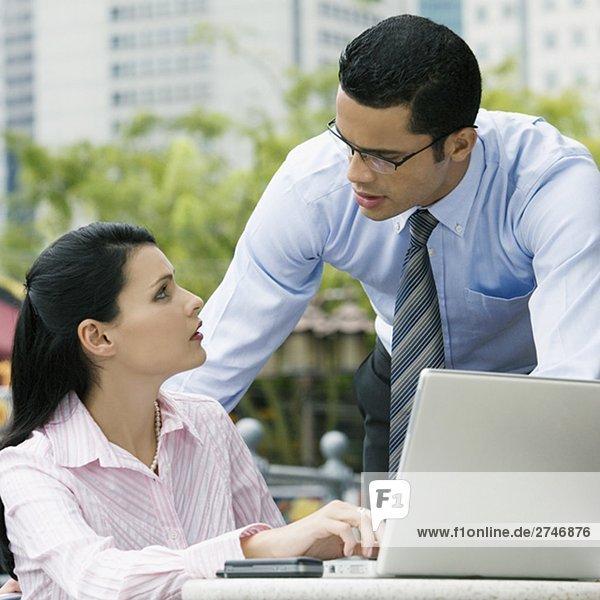 Geschäftsfrau mit einem Laptop mit einem Geschäftsmann neben ihr stehen