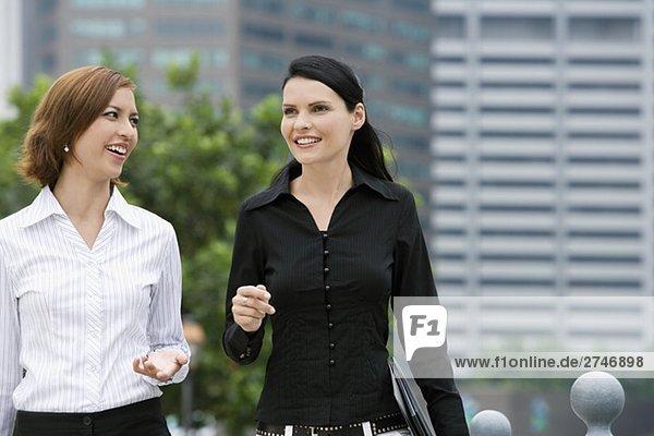 Zwei Geschäftsfrauen zusammen gehen und lächelnd