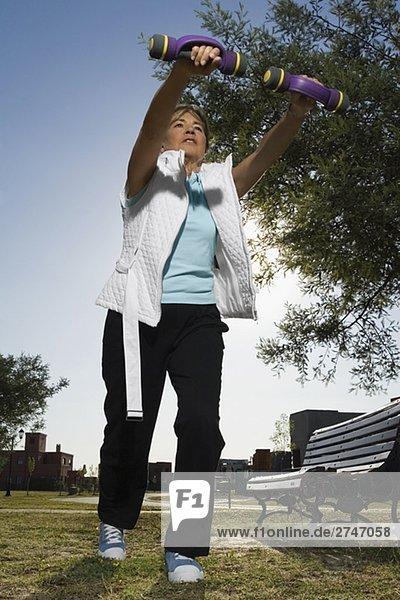 Untersicht of ältere Frau Training mit Hanteln in einem park