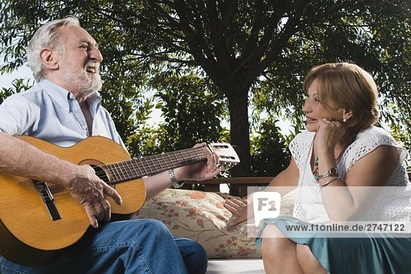 älterer Mann spielen eine Gitarre vor ältere Frau