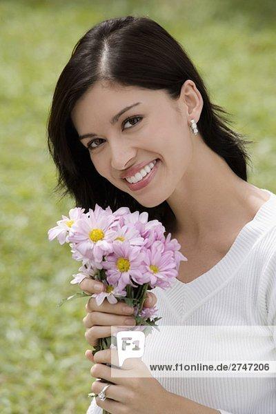 Portrait einer jungen Frau hält einen Blumenstrauß und lächelnd