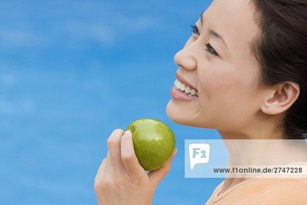 Seitenansicht einer jungen Frau hält einen grünen Apfel