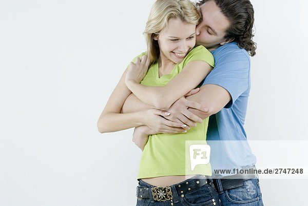 Young man kissing a young woman's cheek