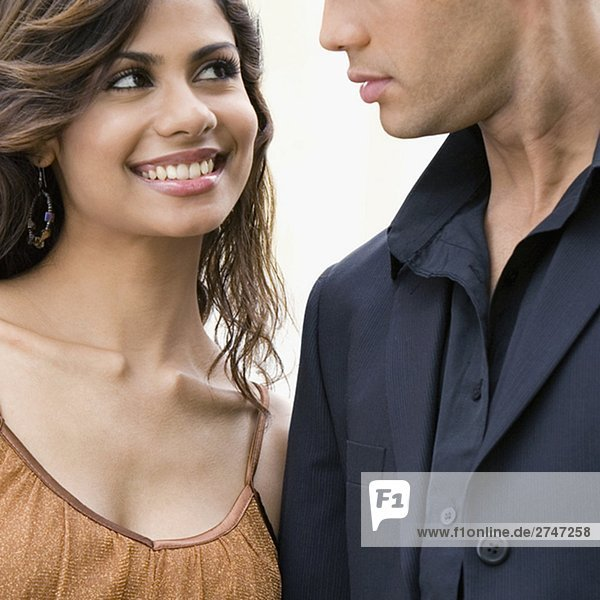 Close-up of a young woman looking at a mid adult man and smiling