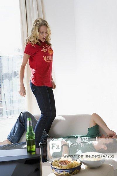 Junge Frau stehend auf einem Sofa mit einem jungen Mann liegen zwischen ihren Beinen