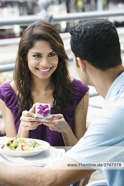 Mid adult man proposing to a young woman at a sidewalk cafe