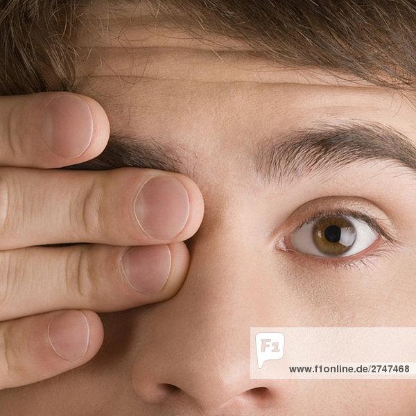 Nahaufnahme eines jungen Mannes mit seinem einem Auge