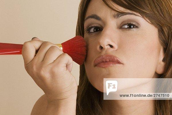 Nahaufnahme einer jungen Frau Anwendung Blush auf ihre Wange