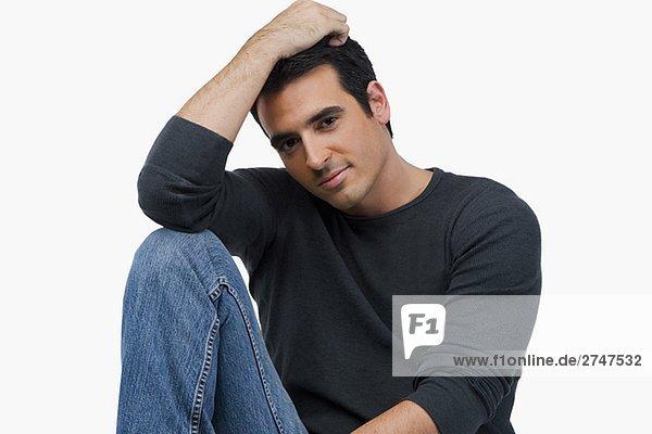 Porträt eines jungen Mannes mit seiner Hand in seine Haare sitzen