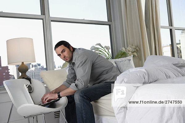 Portrait of a young man sitting on the bed and working on a laptop