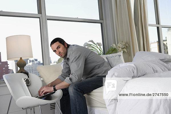 Porträt eines jungen Mannes sitzen auf dem Bett und arbeiten auf einem laptop