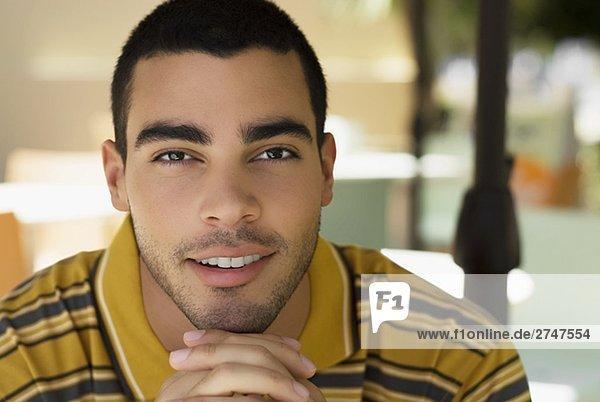 Porträt eines jungen Mannes mit seiner Hände verschränkt lächelnd