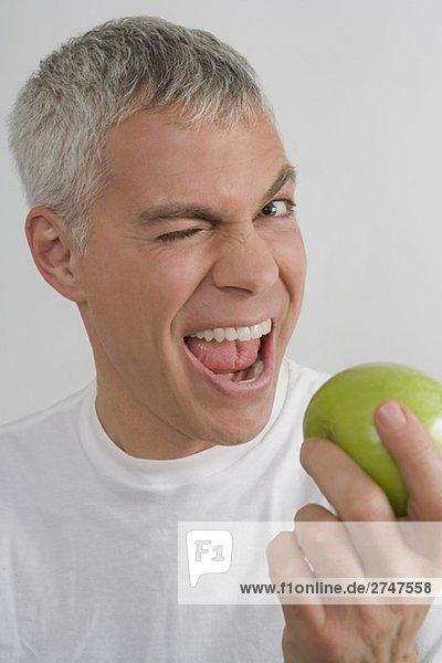 Portrait of a mature Mann hält ein Avocado und zwinkert