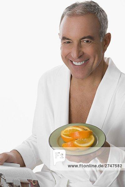 Portrait of a älterer Mann hält einen Teller mit Orange und lächelnd