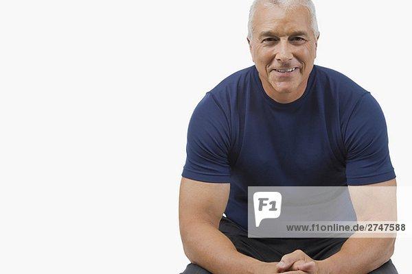 Portrait of a älterer Mann sitzen und seine Hände und lächelnd