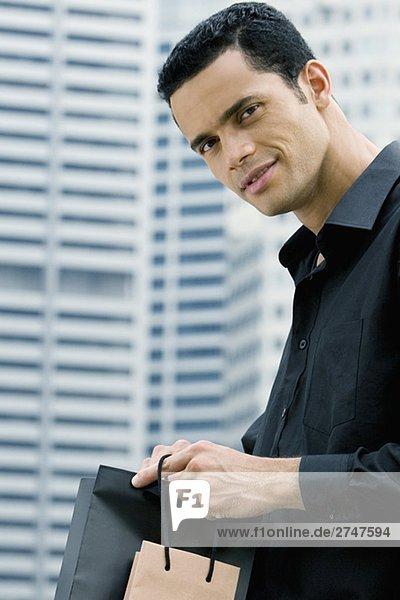 Porträt eines Mitte Erwachsenen Mannes hält Einkaufstaschen und lächelnd