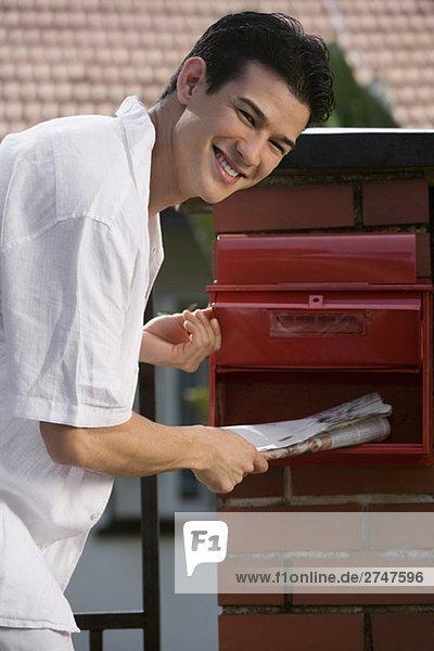 Porträt eines jungen Mannes Überprüfung seiner Mailbox und lächelnd