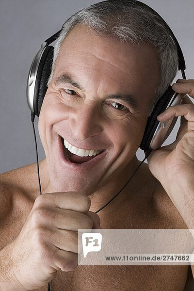 Portrait of a älterer Mann Musikhören mit Kopfhörer und Gesang