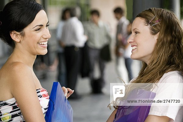 Close-up of two young women looking at each other and smiling
