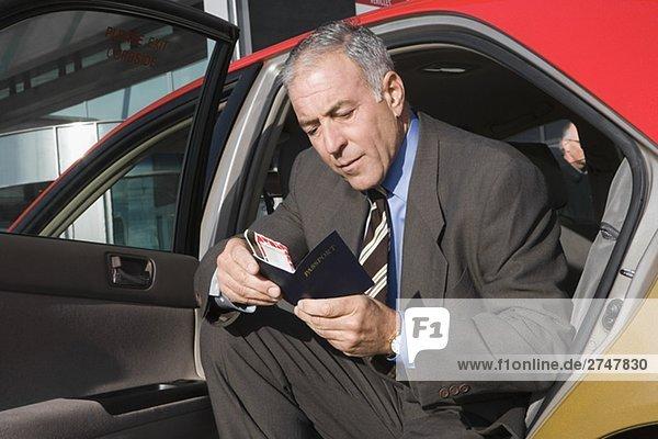 Kaufmann sitzen in einem Taxi und überprüft seinen Pass