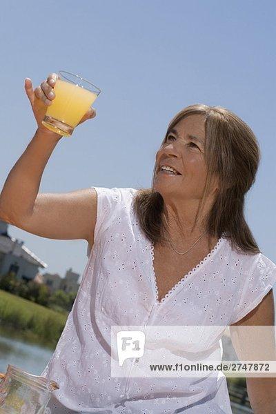 Nahaufnahme of a Seniorin hält Saft und lächelnd