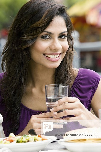 Portrait of a young woman holding a glass of water and smiling
