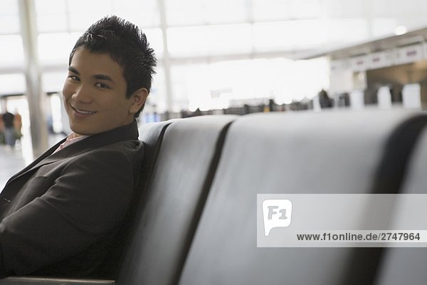Portrait of a businessman sitting at an airport and smiling