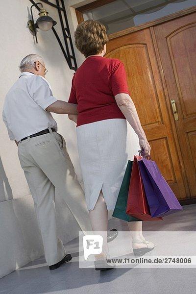 Rückansicht eines senior Paares zu Fuß mit Einkaufstaschen