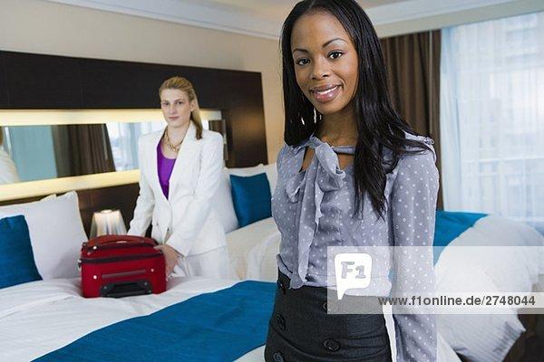 Porträt von geschäftsfrau lächelnd mit einem anderen geschäftsfrau Verpackung ihr Gepäck