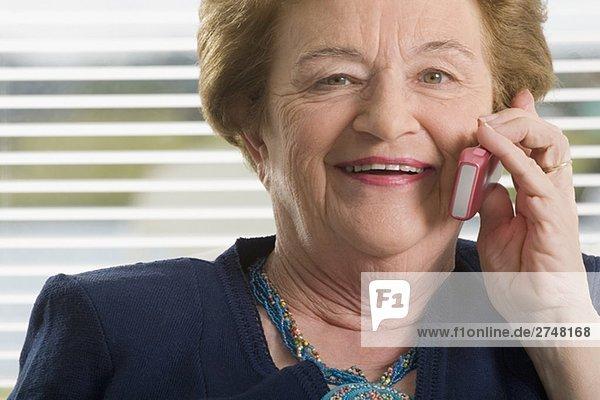 Nahaufnahme of ältere Frau auf einem Mobiltelefon reden und lächelnd