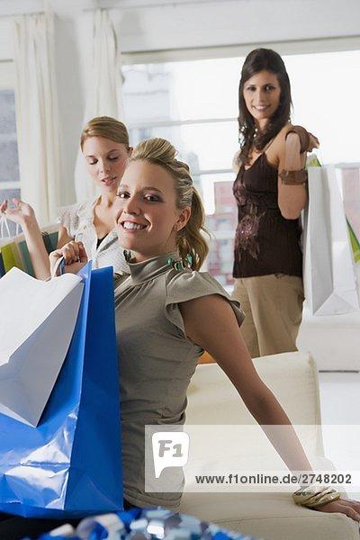 Drei junge Frauen mit Einkaufstüten in einem Wohnzimmer
