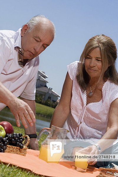 älteres Paar Saft bei Picknick genießen